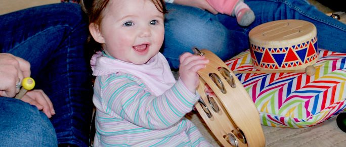 happy-baby-holding-tamborine-music-therapy-session