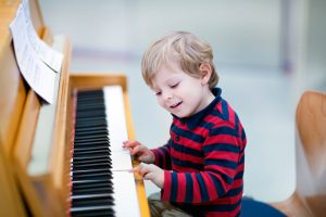 little-boy-additional-needs-at-piano-having-music-therapy