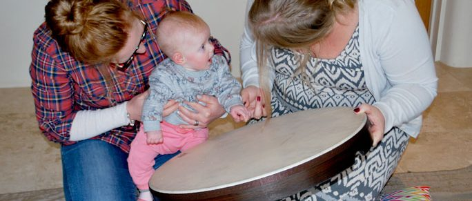 Music-therapist-group-session-baby-parents-smiles-drum